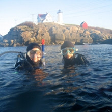 divers in front of lighthouse