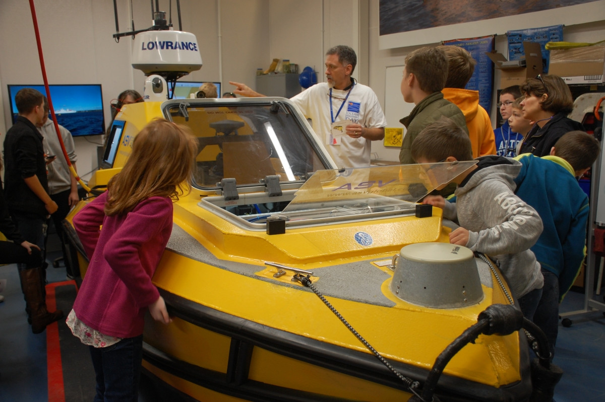Students surround an automated underwater vessel while talking with an ASV representative at Ocean Discovery Day.